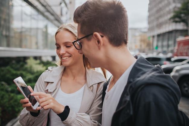 Casal ou amigos rindo engraçado e se divertindo com um telefone inteligente em uma rua da cidade grande.