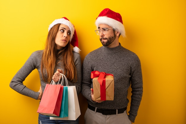 Casal ou amigos segurando presentes e sacolas pensando em uma ideia