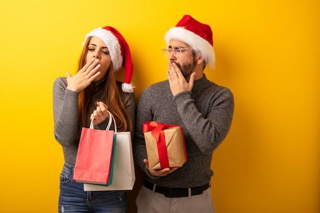 Casal ou amigos segurando presentes e sacos de compras cansados e com muito sono