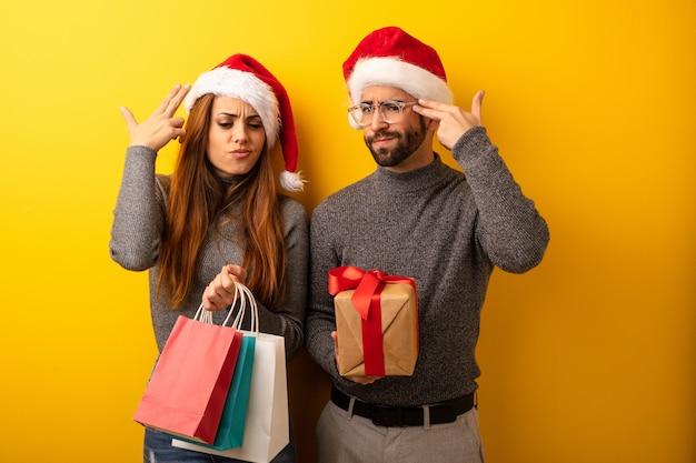 Casal ou amigos segurando presentes e sacos de compras, fazendo um gesto de suicídio