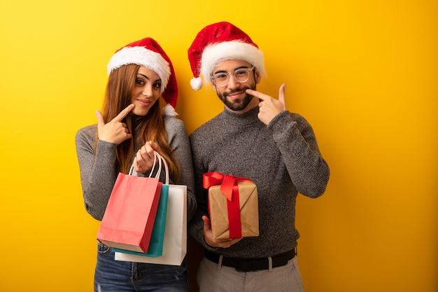 Casal ou amigos segurando presentes e sacos de compras sorrisos, apontando a boca
