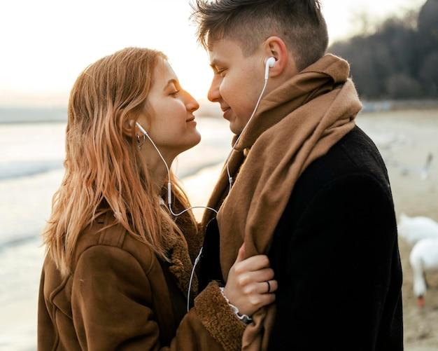 Casal ouvindo música em fones de ouvido na praia no inverno