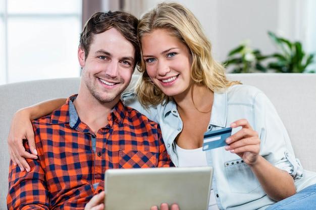 Casal pagando com cartão de crédito no sofá
