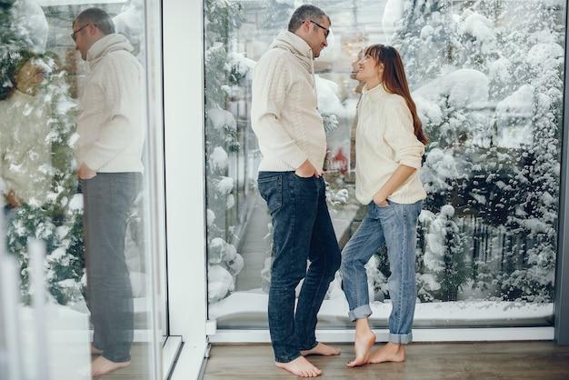 Casal parado perto de uma janela grande em casa