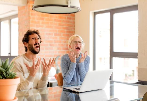 Casal parecendo desesperado e frustrado, estressado, infeliz e irritado, gritando e gritando