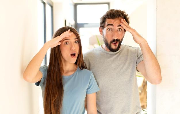 Casal parecendo feliz, espantado e surpreso, sorrindo e percebendo uma boa notícia incrível