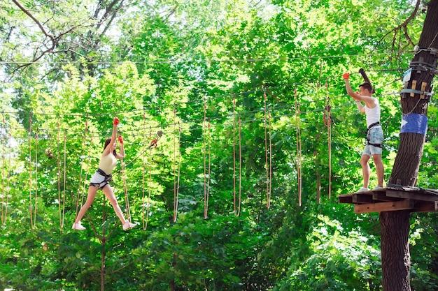 Casal passa seu tempo de lazer em um curso de cordas. homem e mulher envolvidos em escalada,