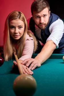 Casal passa um passatempo agradável jogando bilhar juntos, o homem está ensinando uma mulher. descanso em família, entretenimento, conceito de férias