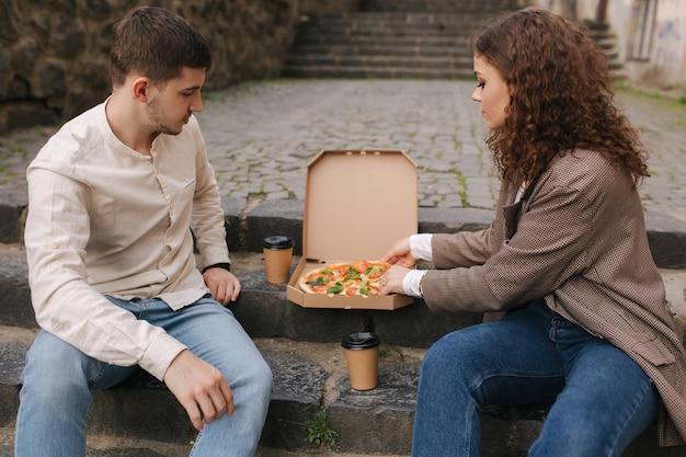 Casal pegando fatias de pizza da caixa ao ar livre