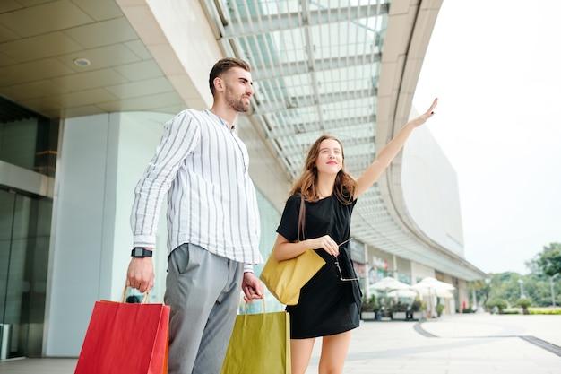 Casal pegando táxi depois de fazer compras