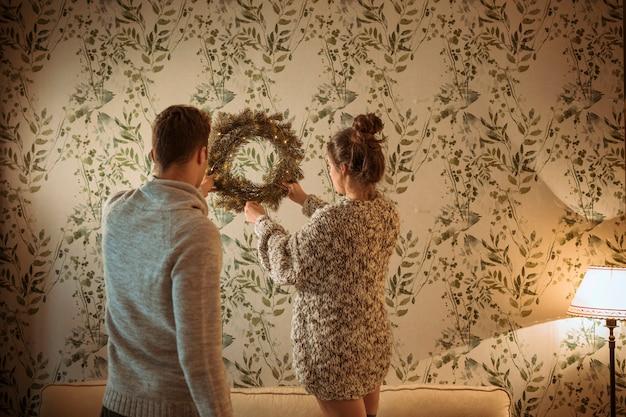 Casal pendurado guirlanda de natal na parede de luz