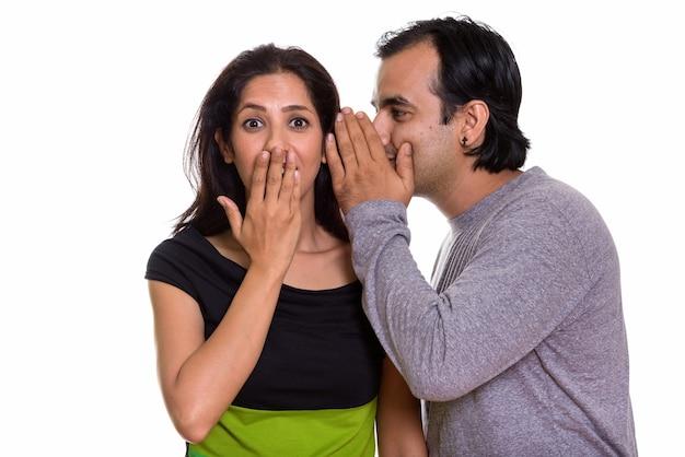 Casal persa com homem sussurrando para mulher