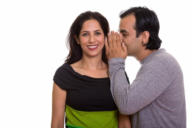Casal persa feliz sorrindo enquanto um homem sussurra para uma mulher