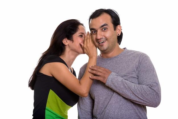 Casal persa feliz sorrindo enquanto uma mulher sussurra para um homem