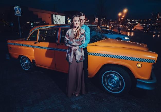 Casal perto de carro de táxi amarelo no período nocturno na rua da cidade