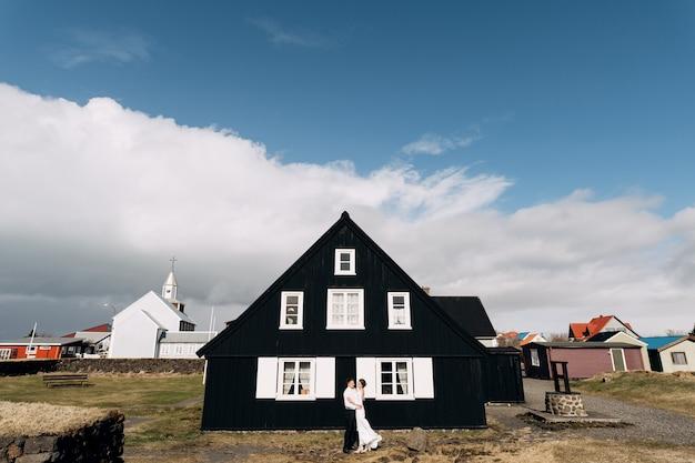 Casal perto de uma casa de madeira preta com janelas e venezianas brancas