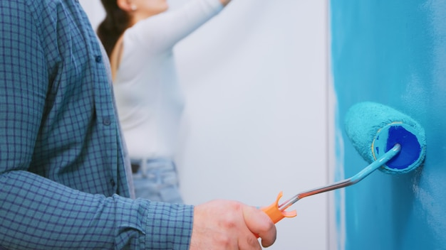 Casal pintando a parede juntos enquanto redecoram a casa. redecoração de apartamento e construção de casa durante a reforma e melhoria. reparação e decoração.