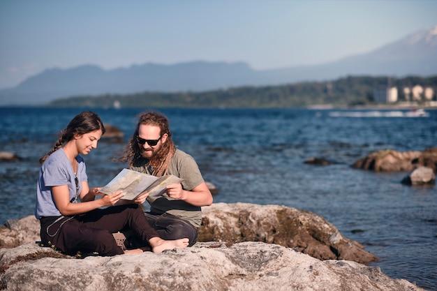 Casal planejando sua viagem olhando um mapa de papel na margem de um lago.