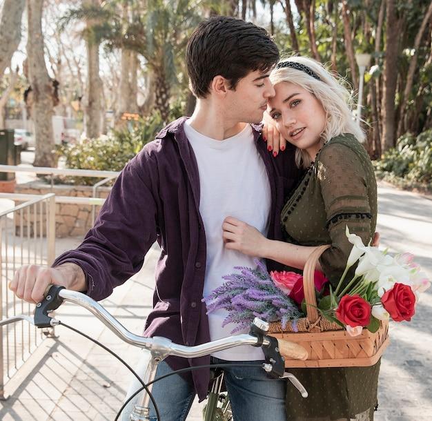 Casal posando ao ar livre com bicicleta e cesta de flores