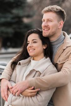 Casal posando ao ser abraçado