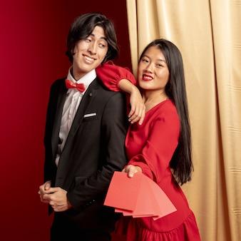 Casal posando com envelopes vermelhos para o ano novo chinês