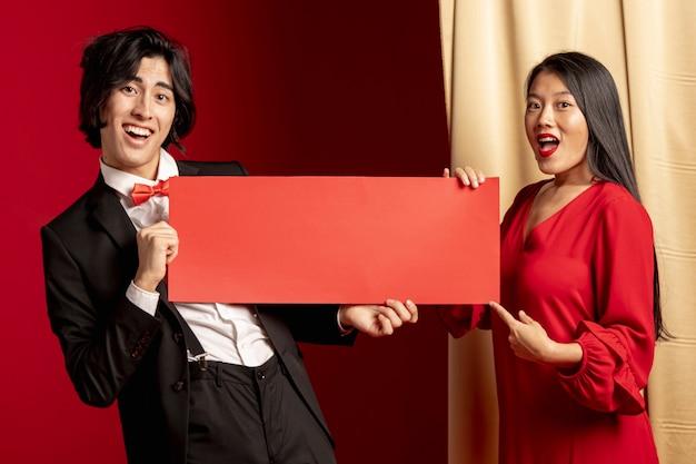 Casal posando com maquete de envelope vermelho para o ano novo chinês