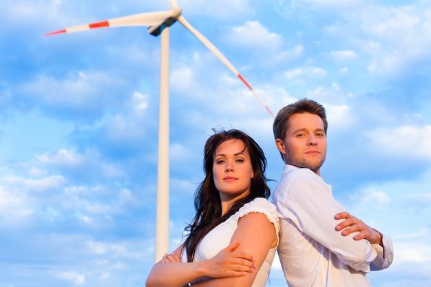 Casal posando com os braços cruzados na frente do moinho de vento