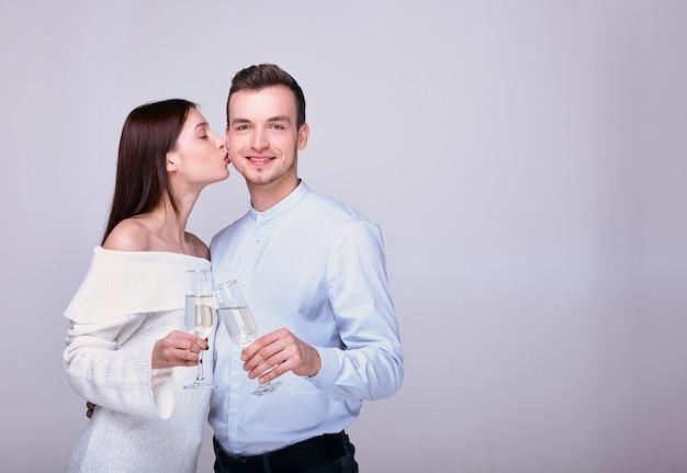 Casal posando com taças de champanhe e uma garota o beija na bochecha em fundo branco