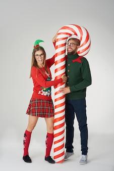 Casal posando com um enorme bastão de doces