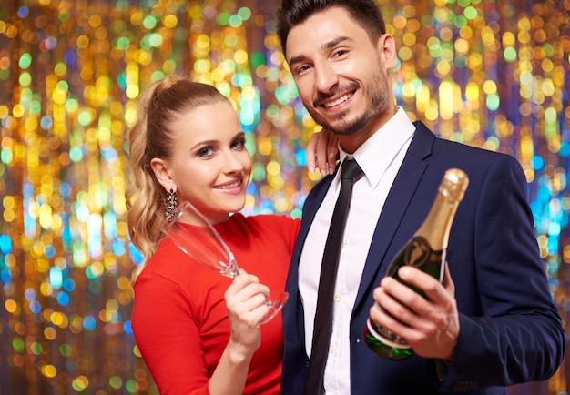Casal posando com uma garrafa de champanhe
