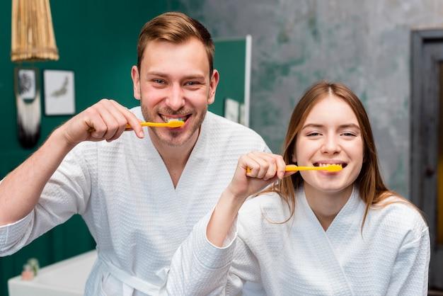 Casal posando em roupões de banho enquanto escova os dentes