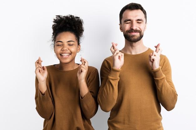 Casal posando enquanto tendo os dedos cruzados