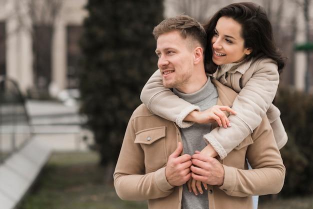 Casal posando juntos ao ar livre