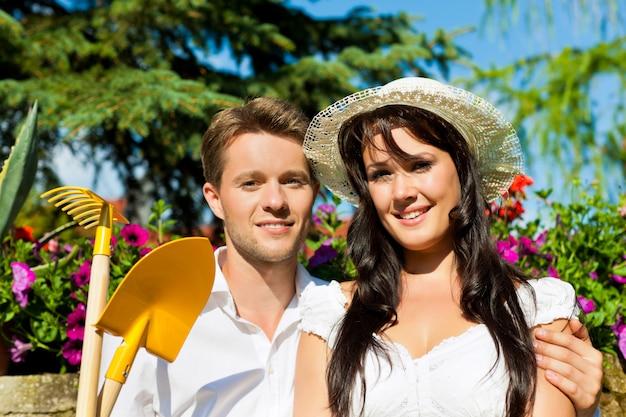 Casal posando na frente de flores com ferramentas de jardinagem