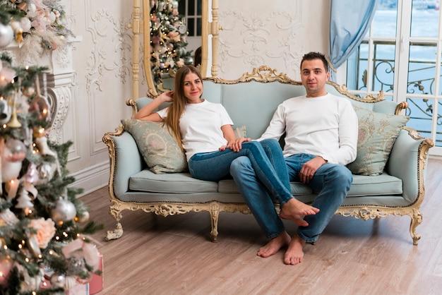 Casal posando no sofá com árvore de natal