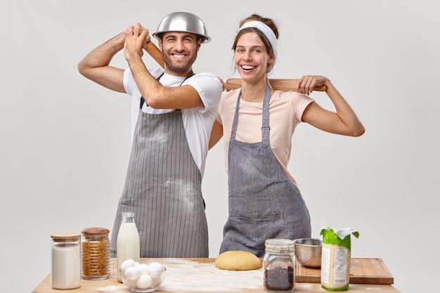 Casal positivo e satisfeito fica perto um do outro perto da mesa da cozinha, usa rolos de massa para fazer massa, asse bolos de biscoito, divirta-se, use aventais sujos de farinha. ficar em casa e cozinhar o jantar