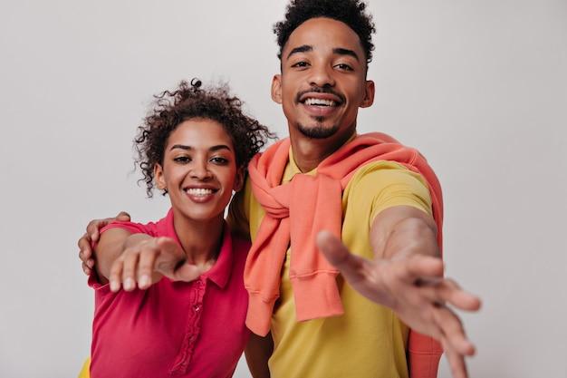 Casal positivo em roupas coloridas pegando a câmera na parede isolada