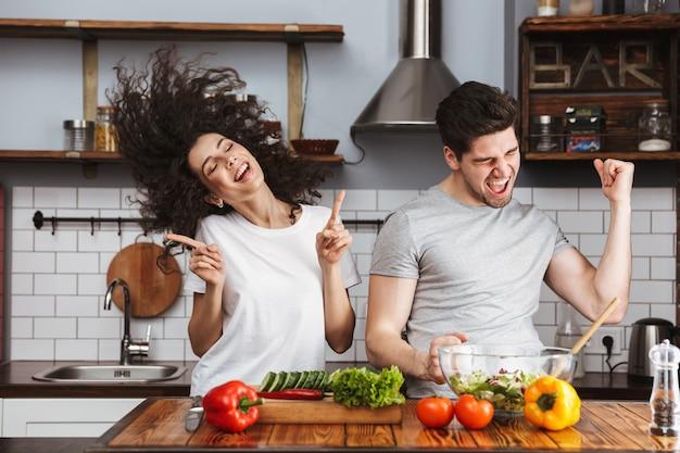 Casal positivo, homem e mulher, cozinhando salat com legumes juntos na cozinha moderna em casa