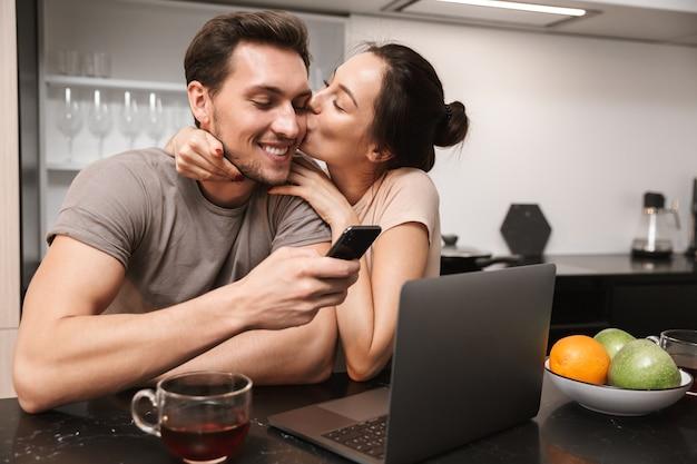 Casal positivo, homem e mulher, usando laptop com smartphone, enquanto está sentado na cozinha