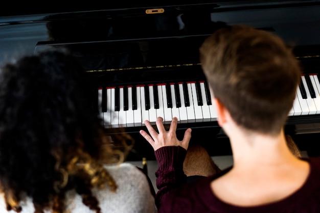 Casal praticando em um piano juntos
