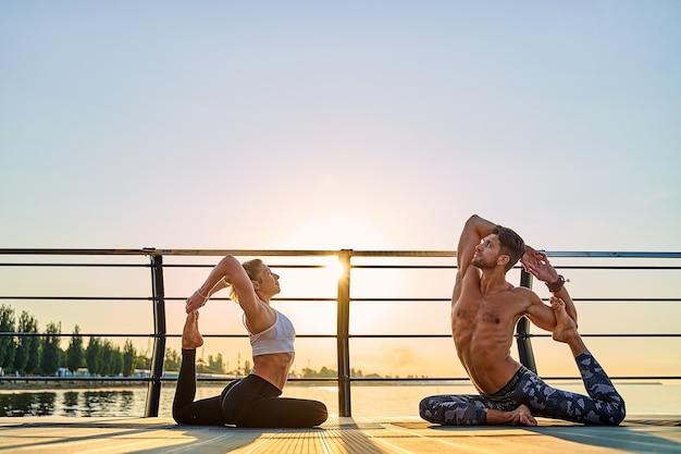 Casal praticando ioga juntos em exercícios matinais ao ar livre na natureza ao nascer do sol