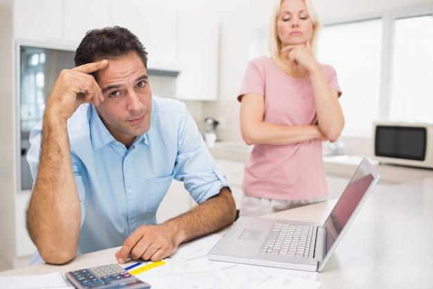 Casal preocupado com contas e laptop na cozinha