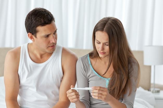 Casal preocupado olhando um teste de gravidez sentado na cama