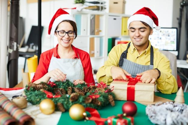 Casal preparando decoração de natal e embrulhando presentes