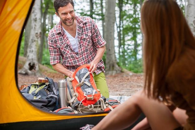 Casal preparando o equipamento para acampar na floresta