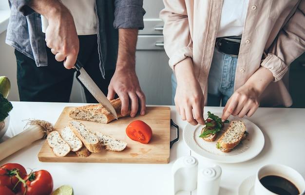 Casal preparando sanduíches enquanto corta pão e vegetais na cozinha