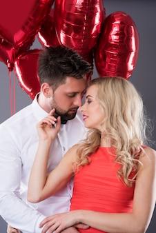 Casal prestes a se beijar entre balões vermelhos