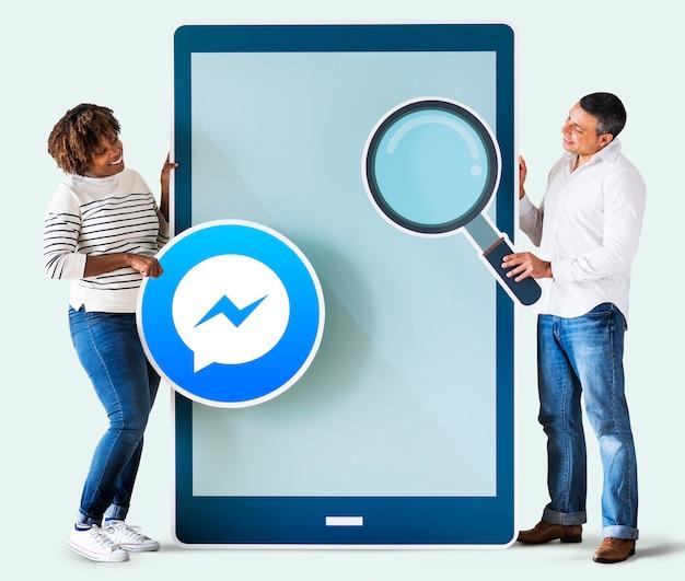 Casal procurando por facebook messenger em um telefone