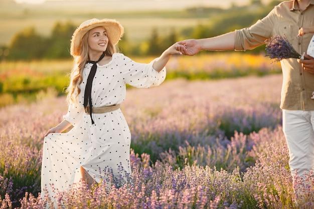 Casal provença relaxando no campo de lavanda. senhora de vestido branco.
