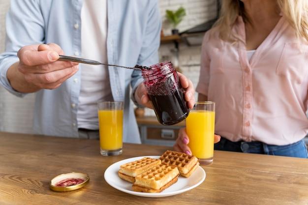 Casal próximo com waffles e geléia
